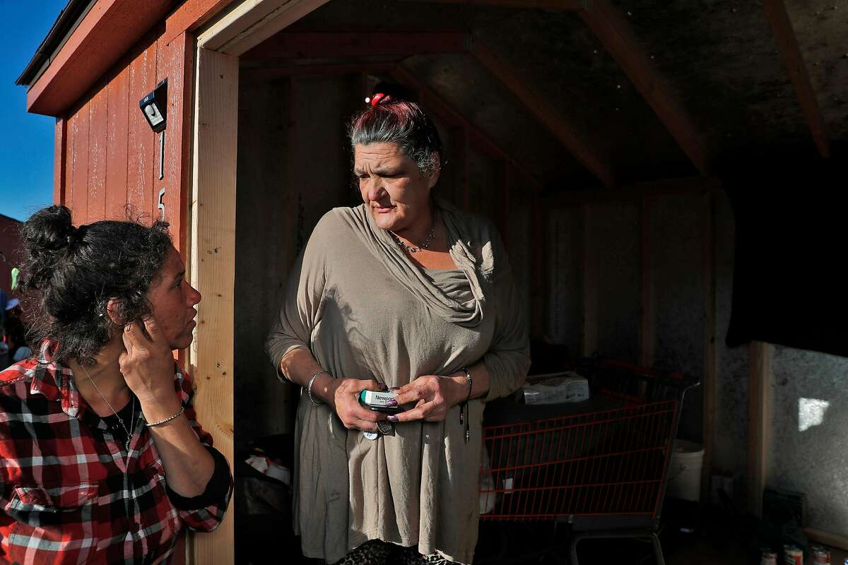 Robyin Clark, right, talks with her daughter Chantal, left, at the shed Robyin shares with her partner Woody West after city officials moved them from their tented homeless camp in Oakland, Calif., on Thursday, December 21, 2017. The couple moved in a few days ago and hopes the city can provide more substantial housing.