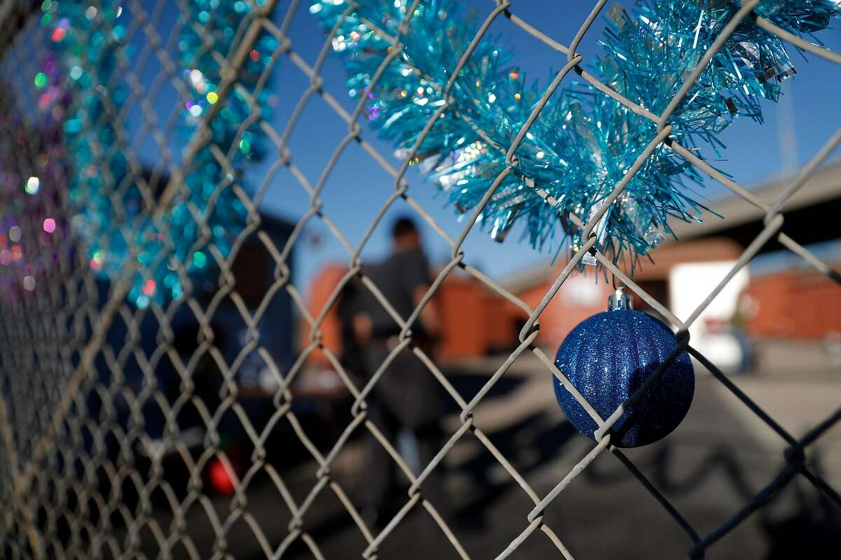 Christmas decoraitons adorn the fence near a new camp at 6th and Castro Streets where Oakalnd city officials moved severl homeless residnets from their tented homeless camp in Oakland, Calif., on Thursday, December 21, 2017. The structures provided by the city are simple garden sheds.