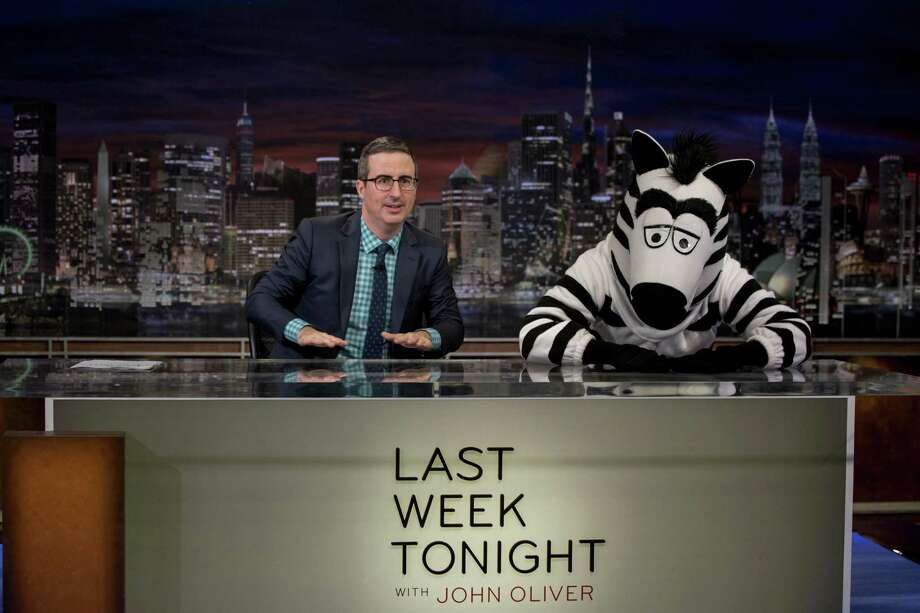 John Oliver with a costumed character on his HBO show. Photo: HBO / Eric Liebowitz