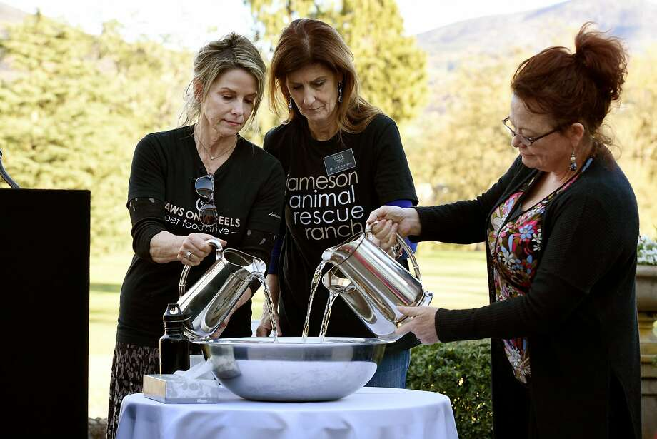 Brenda Burke (left) and Monica Stevens of Jameson Animal Rescue Ranch, and Eileen Harrington ceremonially pour water over a bowl of spirit stones during a memorial for pets and farm animals held at Silverado Resort & Spa in Napa. Photo: Michael Short, Special To The Chronicle