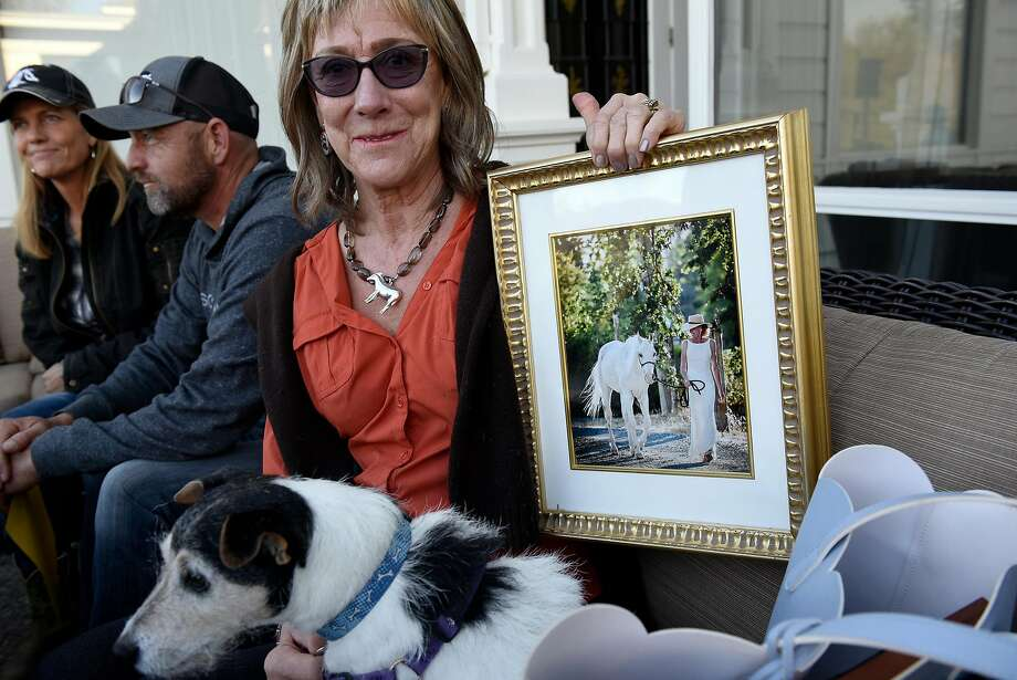 With her dog Katie Bird at her side, Dixie Keith holds a picture of Giorgio, her horse who died in the October blaze. Photo: Michael Short, Special To The Chronicle
