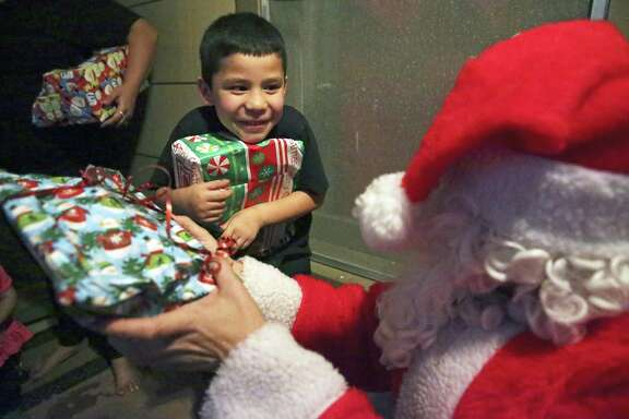 Kobe Salazar giggles in delight while Santa delivers gifts as Louise Locker's holiday program for the poor, the Elf Louise Christmas Project, distributes Christmas gifts to children on the Westside on Dec. 21.