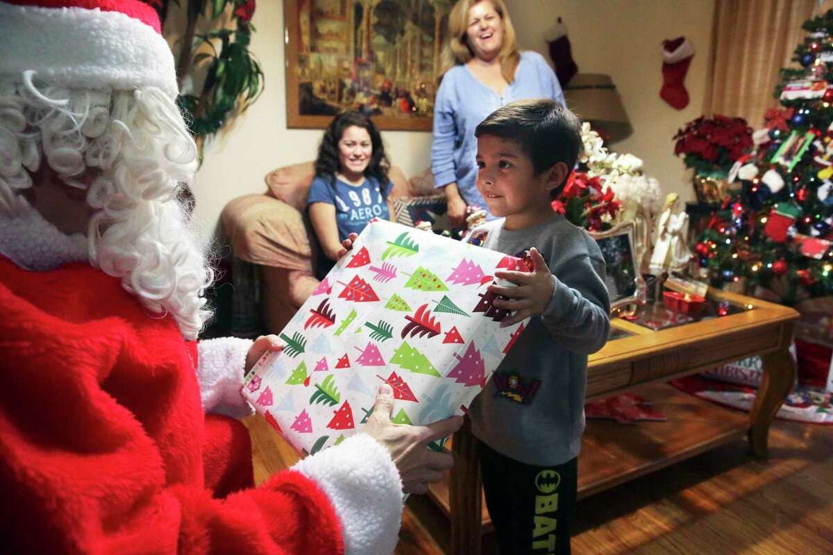"""In this 2017 photo, a child receives a present from Santa through the the Elf Louise Christmas Project. As a child, Louise Locker, the program's founder, would tell her mother, """"Can you imagine if everybody knew the potential for goodness inside of them and they acted upon it, how different the world will be?"""""""