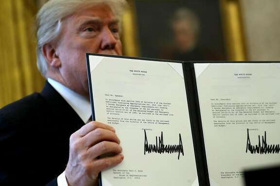 WASHINGTON, DC - DECEMBER 22:  U.S. President Donald Trump holds up a copy of legislation he signed before before signing the tax reform bill into law in the Oval Office December 22, 2017 in Washington, DC. Trump praised Republican leaders in Congress for all their work on the biggest tax overhaul in decades.  (Photo by Chip Somodevilla/Getty Images) ***BESTPIX***