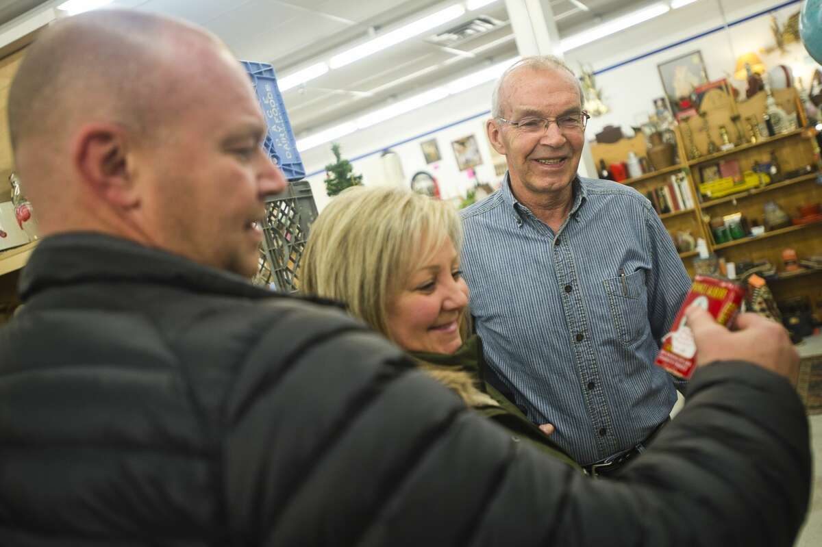 Leo Starks of Three Rivers, right, Tenley Starks of Midland, center, and Steve Starks of Midland, left, check out a vintage tobacco tin on Thursday, Dec. 21, 2017 at the Antique Center, located on the south side of M-20 east of Vance Road. (Katy Kildee/kkildee@mdn.net)