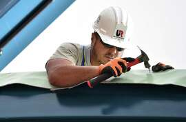 Naugatuck resident Sydney Oliveira, a roofer with United Roofing secures the roofing membrane to the new canopy at Metro-North New Haven State Street Railroad Station at 259 State St. in New Haven, Thursday, June 29, 2017. The new side platform will accomodate the Hartford Line, a commuter rail service that will run between Union Station in New Haven and Springfield, Massachusetts. An official at the site said the project is on schedule to be completed in October. (Catherine Avalone / Hearst Connecticut Media) (Catherine Avalone / Hearst Connecticut Media)