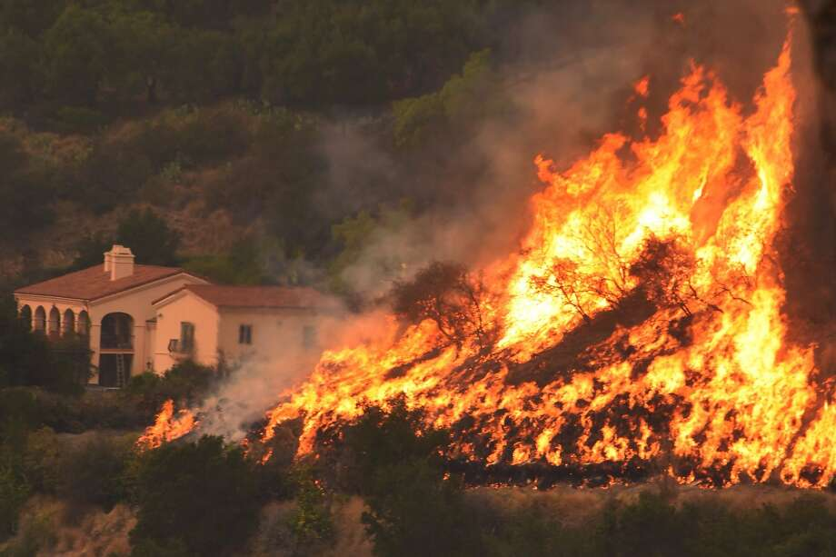 Flames from a back-firing operation rise behind a home off Ladera Lane near Bella Vista Drive in Santa Barbara, Calif. Crews battling Southern California's enormous wildfire are struggling to widen and extend firebreaks before the return of winds Wednesday evening, Dec. 20, 2017, that could once again drive the flames out of control. Photo: Mike Eliason, Associated Press