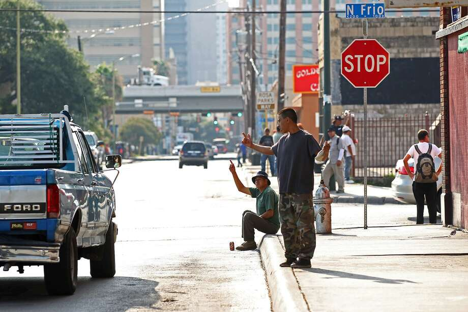 Day workers flag a passing truck while waiting for jobs at the corner of North Frio and West Houston Streets in 2013. San Antonio's economic segregation did not grow in the same way as a whole lot of other cities. Photo: JERRY LARA /San Antonio Express-News / © 2013 San Antonio Express-News