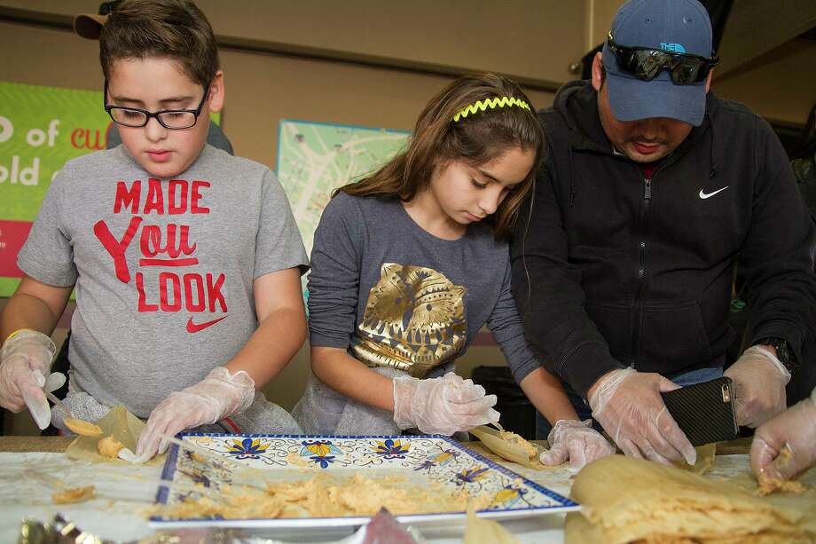 The Herrera family (left to right), brother Papik, 9, sister Xanna, 10, and dad Papik making tamales at the tamale workshop as part of La Gran Tamalada Dec. 10 at Market Square. Photo: Alma E. Hernandez /Alma E. Hernandez / For The San Antonio Express News