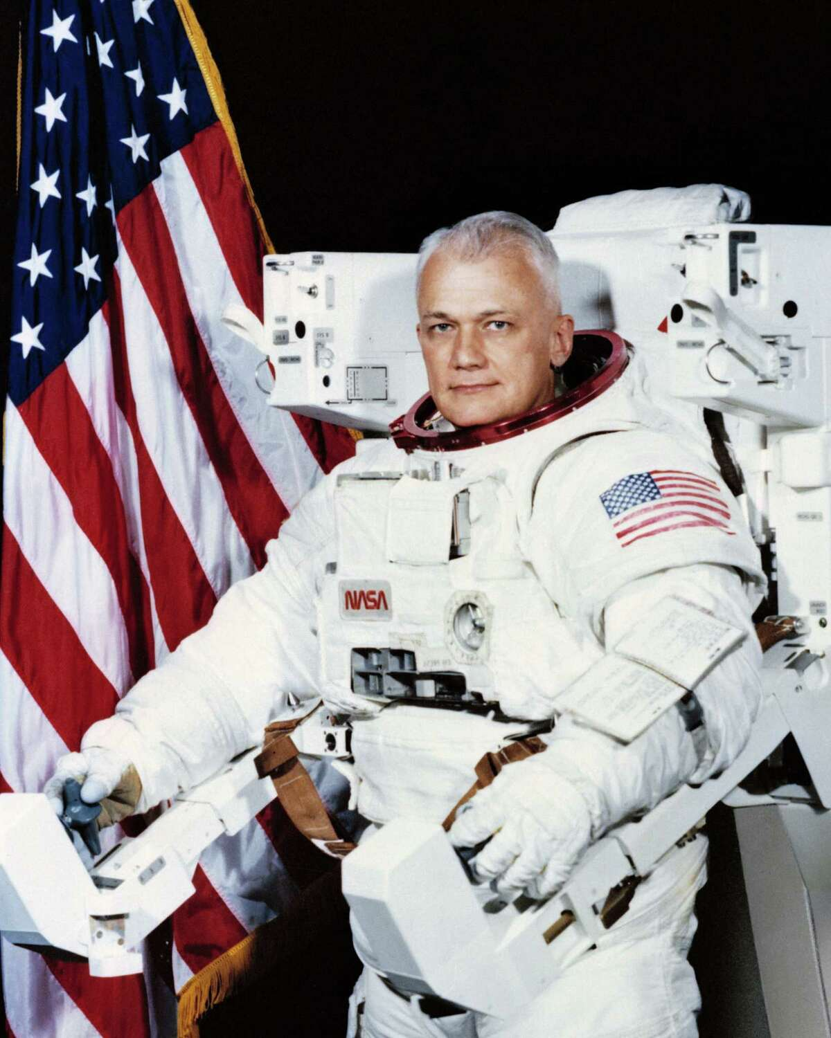 Official Space Shuttle portrait showing Astronaut Bruce McCandless, II, attired in the Shuttle Extravehicular Activity (EVA) Suit with Manned Maneuvering Unit (MMU) attached and American flag in background.