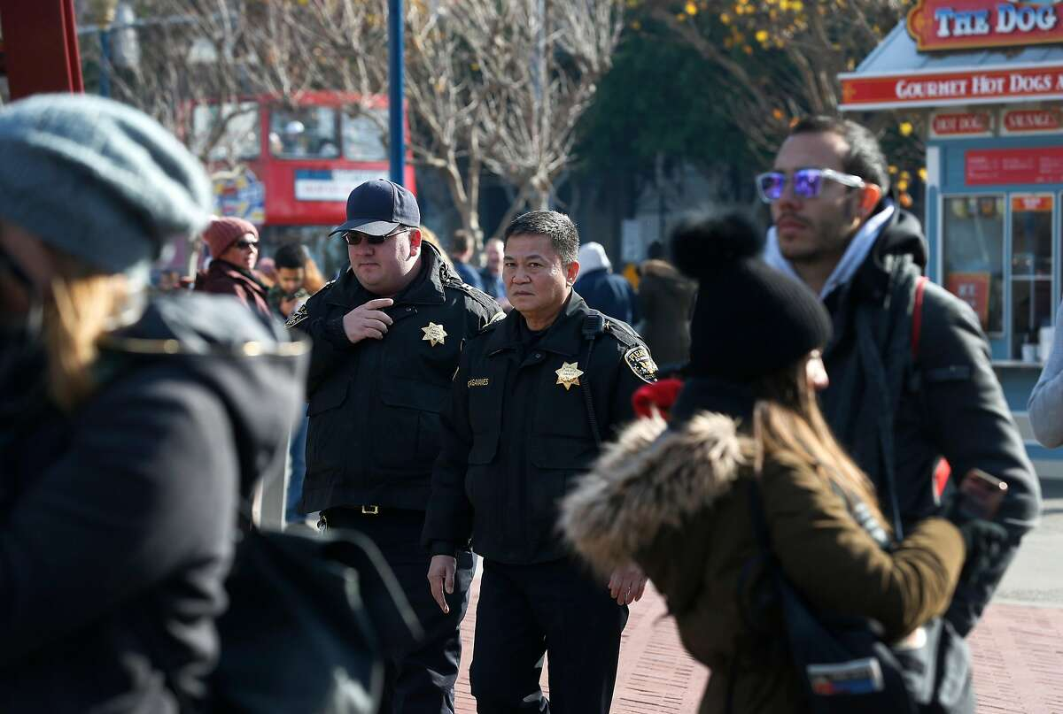 FILE-- Security guards walk through Pier 39 in San Francisco, Calif. on Friday, Dec. 22, 2017. Everitt Aaron Jameson pleaded guilty Monday, June 4, 2018, to attempting to aid a terrorist organization.