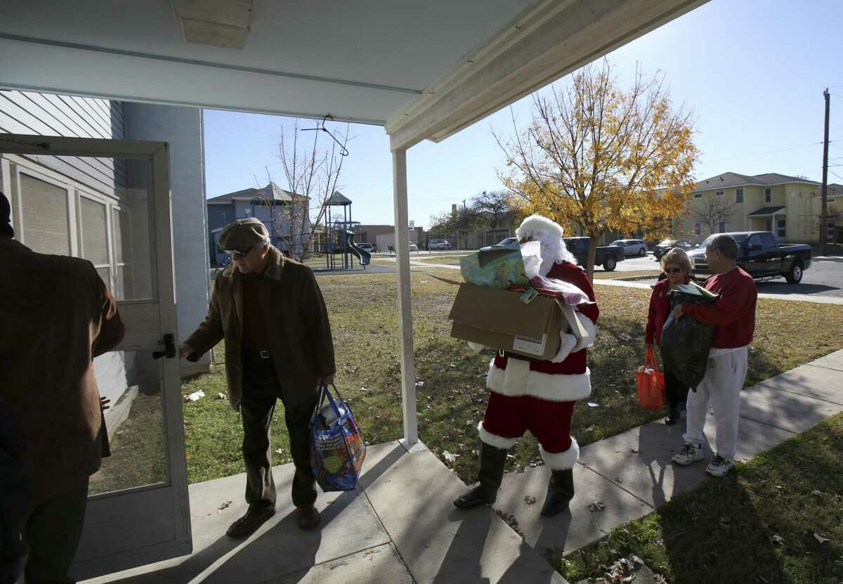 The Ghost Town survivors deliver Christmas presents and food to members of the Sanchez family in December 2013. That was the second year the Ghost Town Survivors sponsored families in their old neighborhood once known as El Ghost Town.