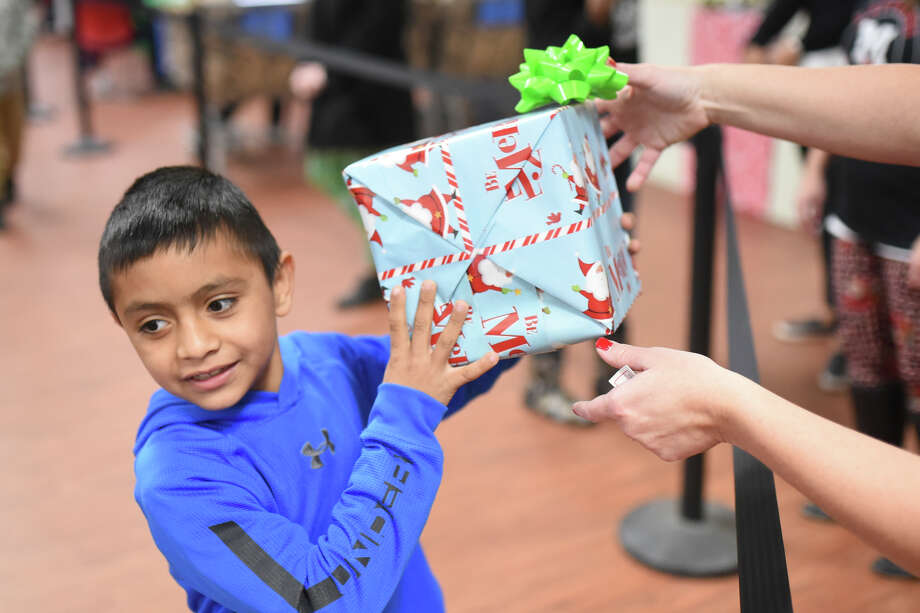 Emmanuel Jimenez, age 8, recieves a present at the annual Christmas lunch on Dec. 22, 2017, at the Midland Soup Kitchen. James Durbin/Reporter-Telegram Photo: James Durbin