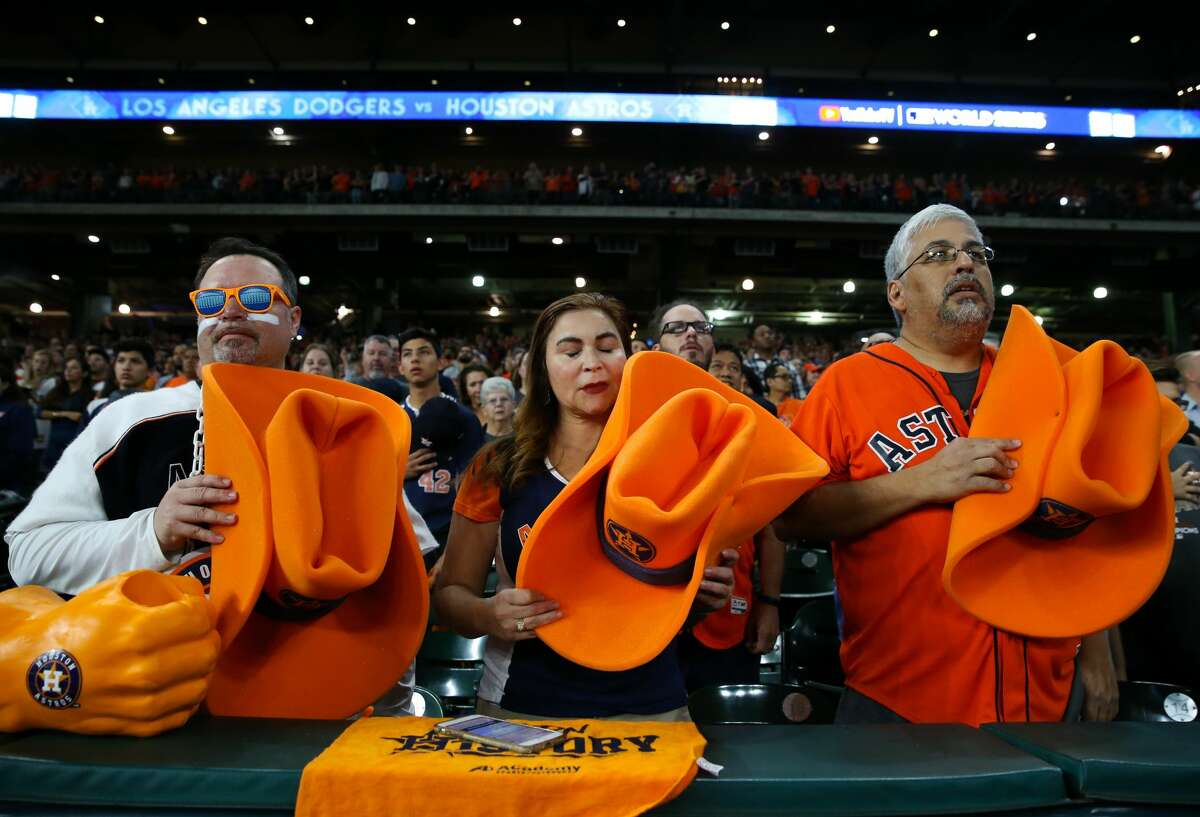 David Arriasola, from left, Debbie Brannon and David Rojas take off their giant orange Astros hats and place them over their heart during National Anthem during the World Series Game 7 Minute Maid Park fan watch party on Wednesday, Nov. 1, 2017, in Houston.