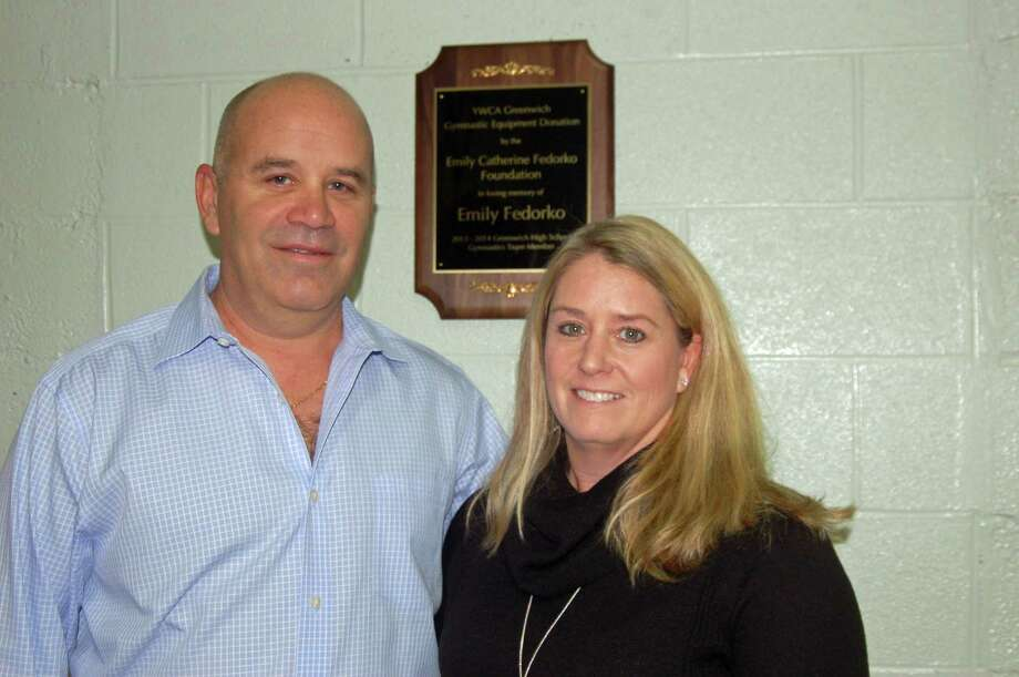 Joe and Pamela Fedorko, parents of Emily Fedorko, stand before the plaque that was hung in the YWCA Greenwich's gymnasium Friday in Emily's honor. Photo: Ken Borsuk /