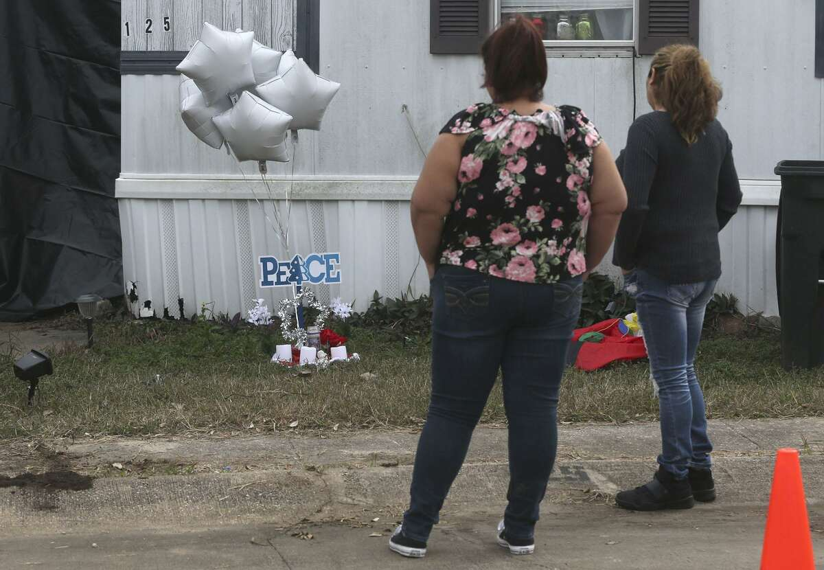 Cecilia Mora (left) and Blanca Martinez (right) pause Friday December 22, 2017 at a manufactured home on the 100 block of Peach Lane in the Pecan Grove Maufactured Home Community in Schertz, Texas where six-year-old Kameron Prescott was shot. Prescott was shot while inside his home in the 100 block of Peach Lane. Four Bexar County deputies had been chasing a wanted felon in the area, and they opened fire on her as she tried to break into Prescott's home. The woman, who has not been identified, was killed. Martinez said she placed the six balloons there bacause Prescott was six-years-old.