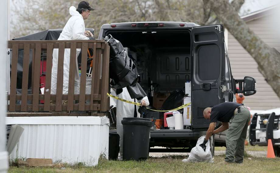 A county detective (right) looks through a garbage bag Friday December 22, 2017 at a manufactured home on the 100 block of Peach Lane in the Pecan Grove Maufactured Home Community in Schertz, Texas where six-year-old Kameron Prescott was shot. Prescott was shot while inside his home in the 100 block of Peach Lane. Four Bexar County deputies had been chasing a wanted felon in the area, and they opened fire on her as she tried to break into Prescott's home. The woman, who has not been identified, was killed. Photo: John Davenport, STAFF / San Antonio Express-News / ©John Davenport/San Antonio Express-News