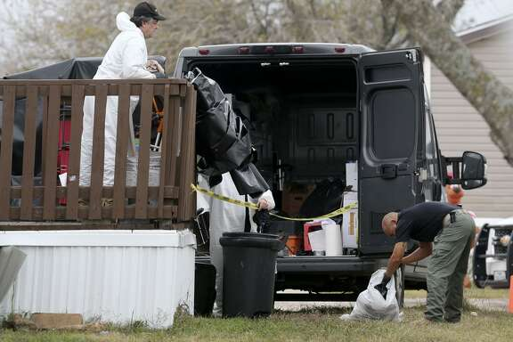A county detective (right) looks through a garbage bag Friday December 22, 2017 at a manufactured home on the 100 block of Peach Lane in the Pecan Grove Maufactured Home Community in Schertz, Texas where six-year-old Kameron Prescott was shot. Prescott was shot while inside his home in the 100 block of Peach Lane. Four Bexar County deputies had been chasing a wanted felon in the area, and they opened fire on her as she tried to break into Prescott's home. The woman, who has not been identified, was killed.