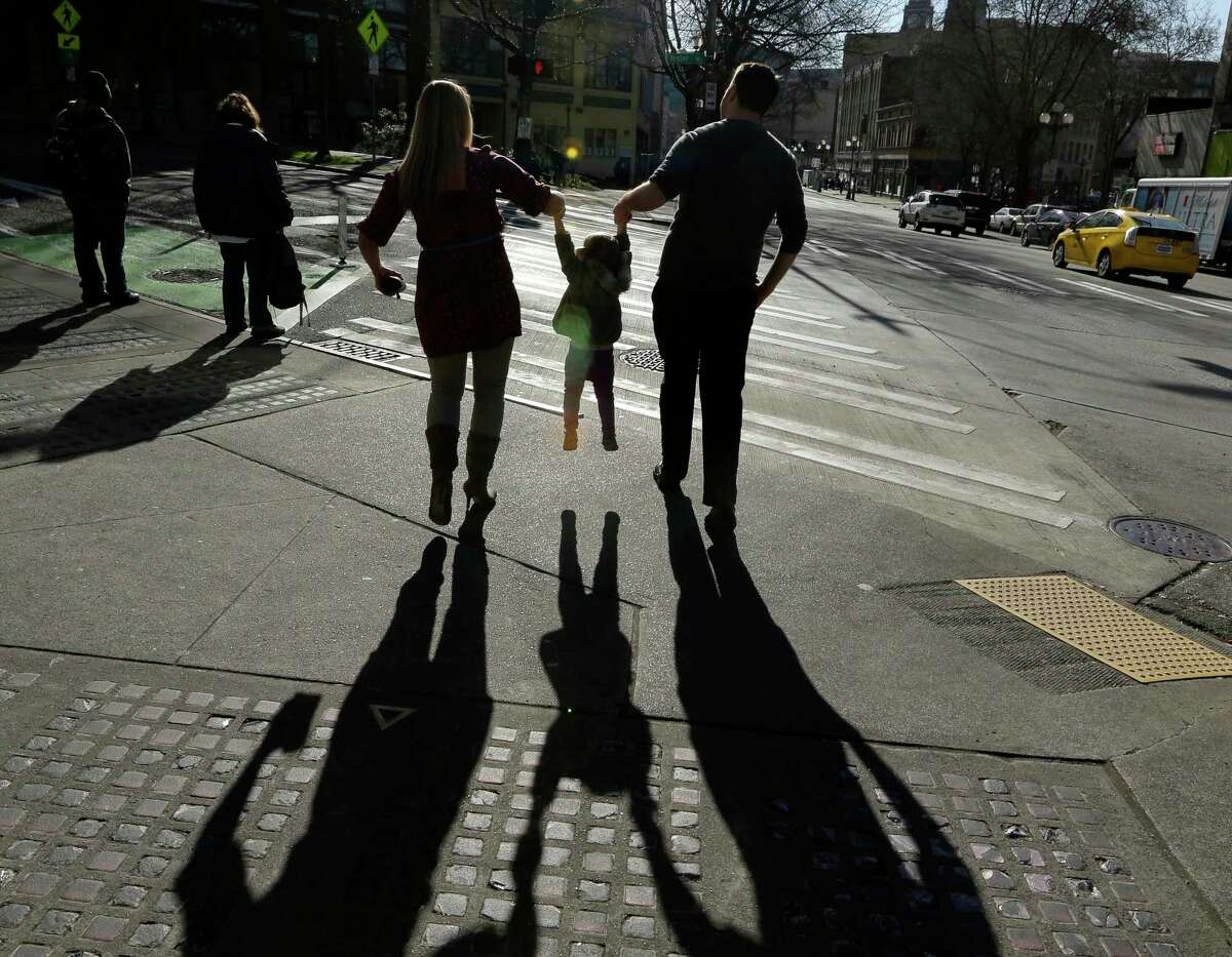 FILE - In this March 3, 2015, file photo, a child is lifted by her parents at a street corner in downtown Seattle. The expansion of a child tax credit helped seal CongressÂ?' approval of the Republican tax overhaul. (AP Photo/Ted S. Warren, File)