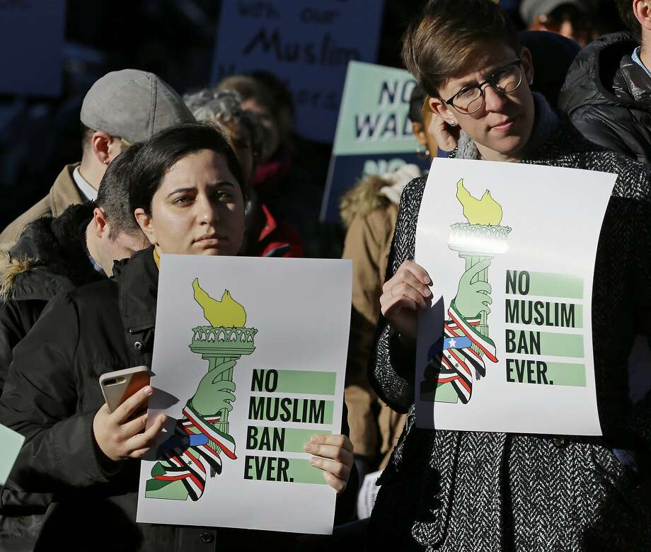 """Mana Rostami-Mouripour, left, and Sara Sluszka, right, both of Seattle, hold signs that read """"No Muslim Ban Ever,"""" during a protest, Wednesday, Dec. 6, 2017, outside a federal courthouse in Seattle. The U.S. Supreme Court decision allowing President Donald Trump's third travel ban to take effect has intensified the attention on a legal showdown Wednesday before three judges in Seattle who have been cool to the policy as they hear arguments in Hawaii's challenge to the ban, which restricts travel to the United States by residents of six mostly Muslim countries and has been reviled by critics as discriminatory. (AP Photo/Ted S. Warren) Photo: Ted S. Warren, Associated Press"""