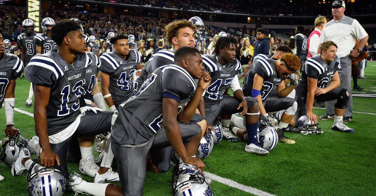 West Orange-Stark players kneel on the field after losing to Pleasant Grove in the Class 4A Division II state final at AT&T Stadium in Arlington on Friday. Photo taken Friday 12/22/17 Ryan Pelham/The Enterprise