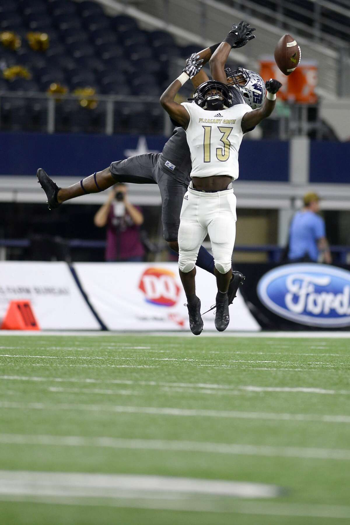 West Orange-Stark?•s Deiondr?•e Hawthorne and Pleasant Grove's Tyler Kelley leap for a pass during the second quarter against in the Class 4A Division II state final at AT&T Stadium in Arlington on Friday. Photo taken Friday 12/22/17 Ryan Pelham/The Enterprise