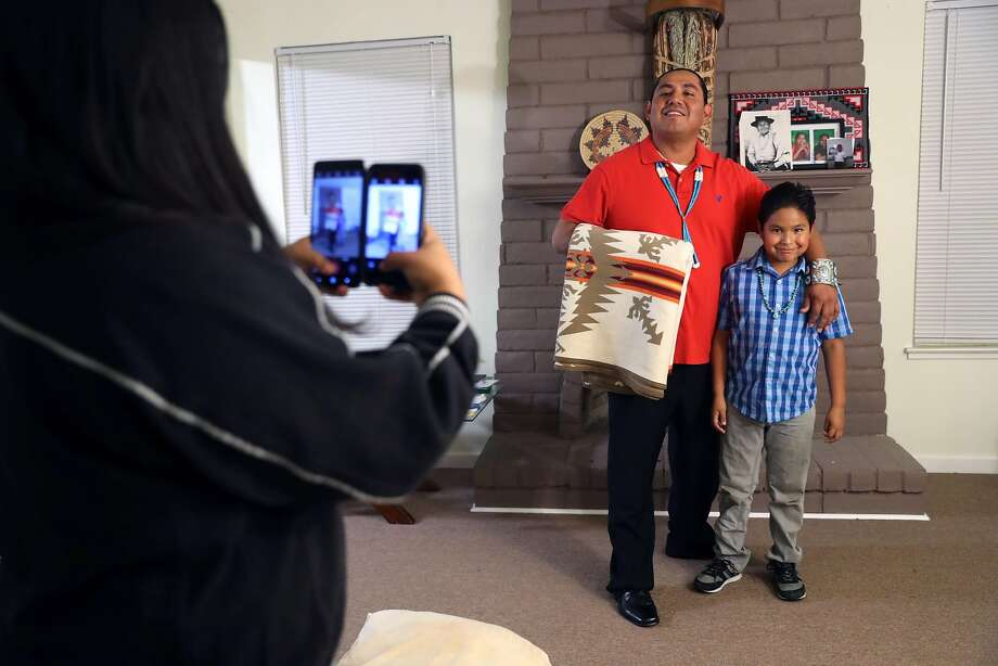 Sage Chief, 12, photographs her father, Joshua Perez, and brother Kinyaanii Chief, 8, at their home. Perez's broken leg sapped his income as a contractor. Photo: Scott Strazzante, The Chronicle