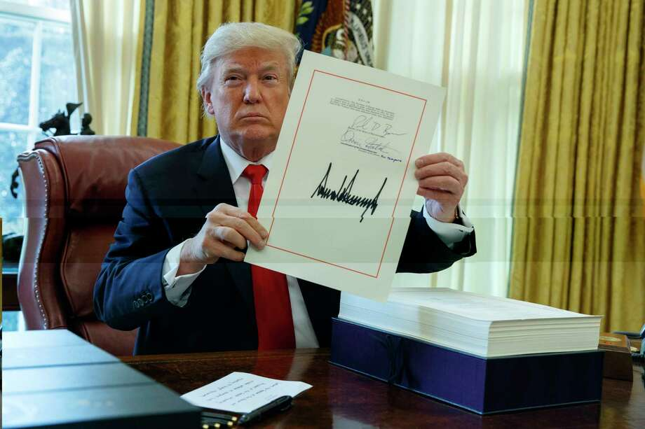 President Donald Trump shows off the tax bill after signing it in the Oval Office of the White House, Friday, Dec. 22, 2017, in Washington. (AP Photo/Evan Vucci) Photo: Evan Vucci / Copyright 2017 The Associated Press. All rights reserved.