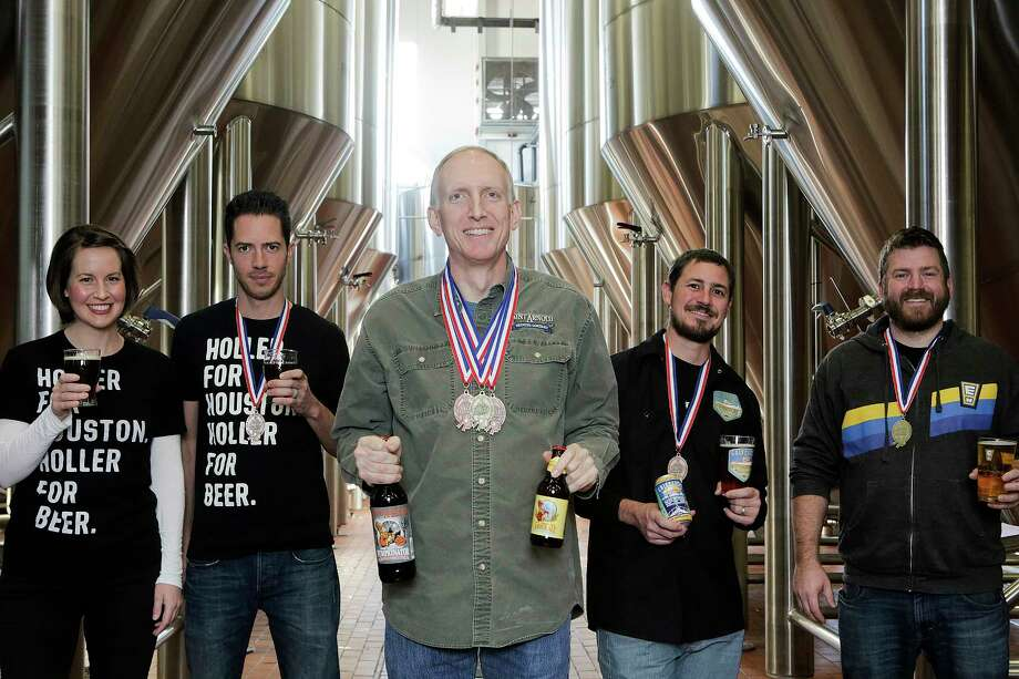 Award-winning Houston brewers pose for a photo at Saint Arnold Brewing Co. on   Friday, Dec. 8, 2017, in Houston. They include Karhryn (from left) and John Holler of Holler Brewing, Brock Wagner, owner of Saint Arnold, Mark Dell'Osso of Galveston Island Brewing and Casey Motes of Eureka Heights Brew Co.  ( Elizabeth Conley / Houston Chronicle ) Photo: Elizabeth Conley, Chronicle / © 2017 Houston Chronicle