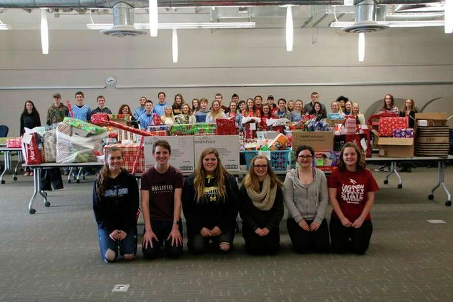 Meridian Early College High School students pose with a portion of the gifts collected for the 10 families the school adopted for the holidays. (Photo provided)