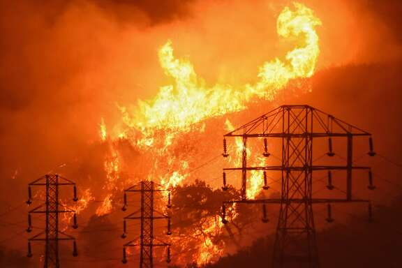 In this Dec. 16, 2017, photo provided by the Santa Barbara County Fire Department, flames burn near power lines in Sycamore Canyon near West Mountain Drive in Montecito, Calif. The huge wildfire that burned hundreds of homes in Santa Barbara and Ventura counties is now the largest in California's recorded history. State fire officials said Friday, Dec. 22, 2017, that the Thomas fire has scorched 273,400 acres, or about 427 square miles of coastal foothills and national forest. That was 154 acres larger than the 2003 Cedar fire in San Diego that killed 15 people. Thousands of firefighters and fleets of aircraft have been battling the blaze since Dec. 4. A firefighter and a woman fleeing the blaze died. (Mike Eliason/Santa Barbara County Fire Department via AP)