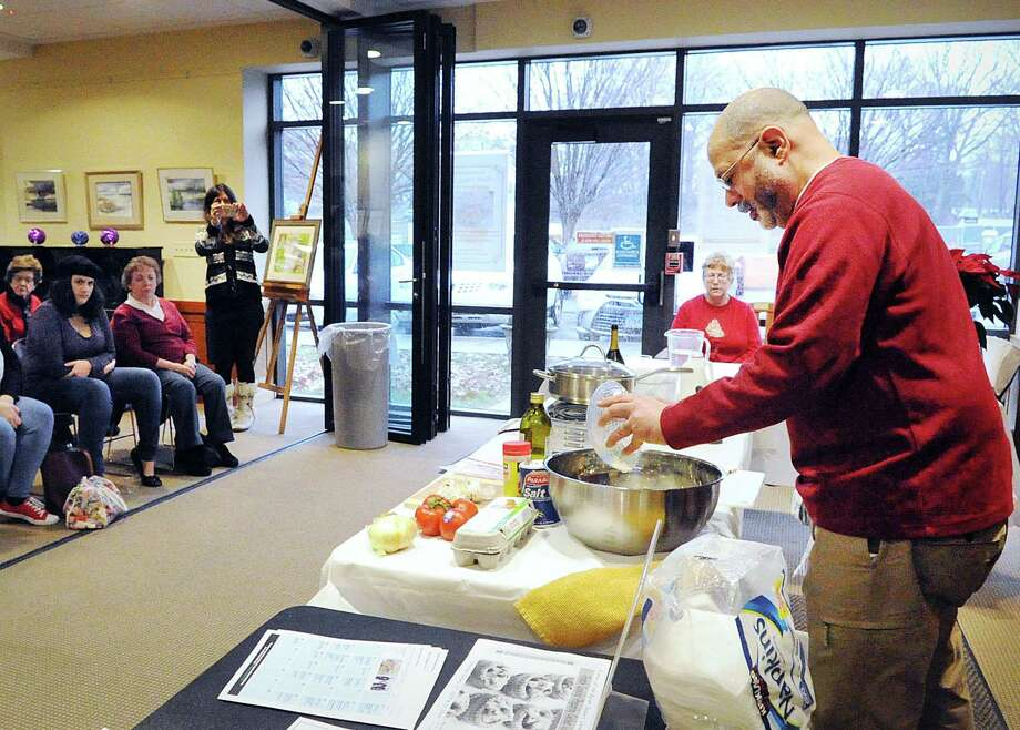Christmas breakfast cooking demonstration by Byram Shubert Librarian Miguel Garcia-Colon, pictured here at right, and Barbara O'Toole at Byram Shubert Library in Greenwich, Conn., Saturday morning, Dec. 23, 2017. Fifty people attended the cooking event sponsored by the Friends of the Byram Shubert Library organization. Garcia-Colon cooked his Christmas specialty, fluffy eggs breakfast with garlic, tomatoes and ham. O'Toole demonstrated two of her favorite holiday dishes, a breakfast casserole and egg strata. Photo: Bob Luckey Jr. / Hearst Connecticut Media / Greenwich Time