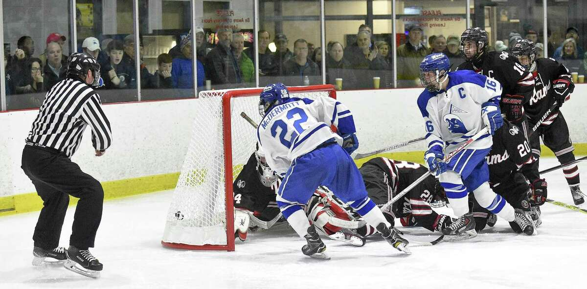 Darien Bennett McDermott (22) finds the outside corner of the net to score on New Canaan goalie Jack Spain during a FCIAC boys ice hockey game at the Darien Ice Rink in Darein, Conn. on Saturday, Dec. 23, 2017. Darien defeated New Canaan 8-1.