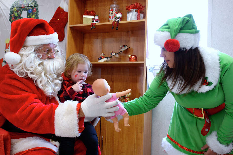 Kate Crane, 2, receives a gift from Santa, played by Ricky Winger, and elf Kourtney Kirkendall during Bevil Oaks' Christmas celebration on Saturday. Each child received a gift and bag of cookies from Santa Claus, and drawings were held for larger gifts like bikes.  Photo taken Saturday 12/23/17 Ryan Pelham/The Enterprise Photo: Ryan Pelham / ©2017 The Beaumont Enterprise/Ryan Pelham