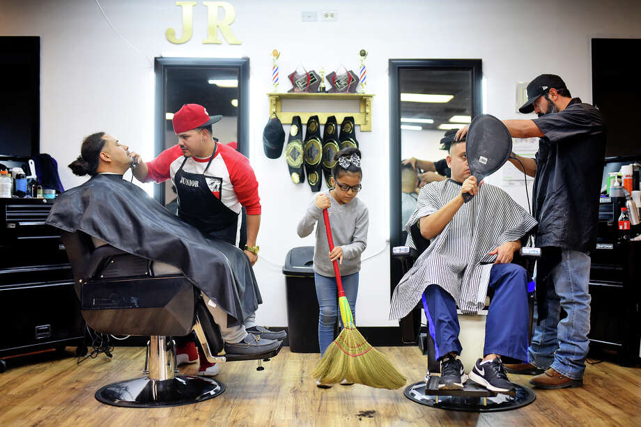Legendz Barbershop owners Junior Guevara (left) and Lupe Meraz (right), cut hair Dec. 23, 2017. Junior's daughter Bella, age 10, helps out at the new business by sweeping hair. Guevara and Meraz have won title belts in hair-cutting competitions, visible hanging in background. Legendz Barbershop is located in the Westwood Village plaza near the intersection of Midland Drive and Illinois Ave. James Durbin/Reporter-Telegram Photo: James Durbin