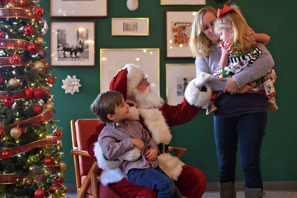 Members of the Yates family meet Santa Claus during a cookies and cocoa with Santa event Dec. 23, 2017 at Opal's Table restaurant in downtown Midland. James Durbin/Reporter-Telegram