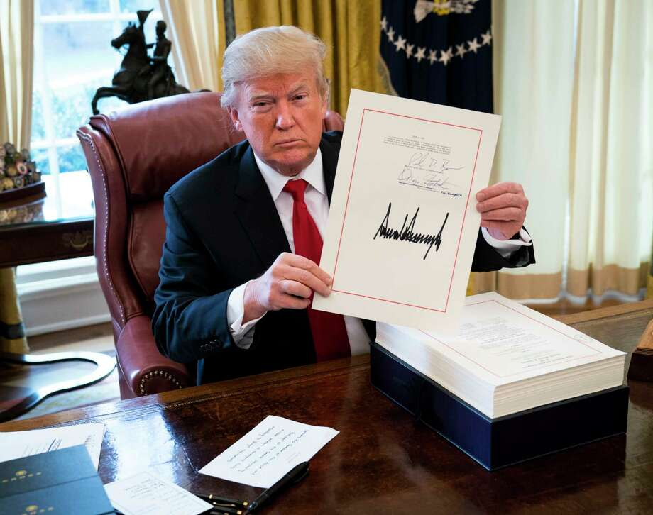 President Donald Trump displays his signature on a sweeping tax bill on Friday that Republicans promise will benefit the middle class. Photo: DOUG MILLS, STF / NYTNS