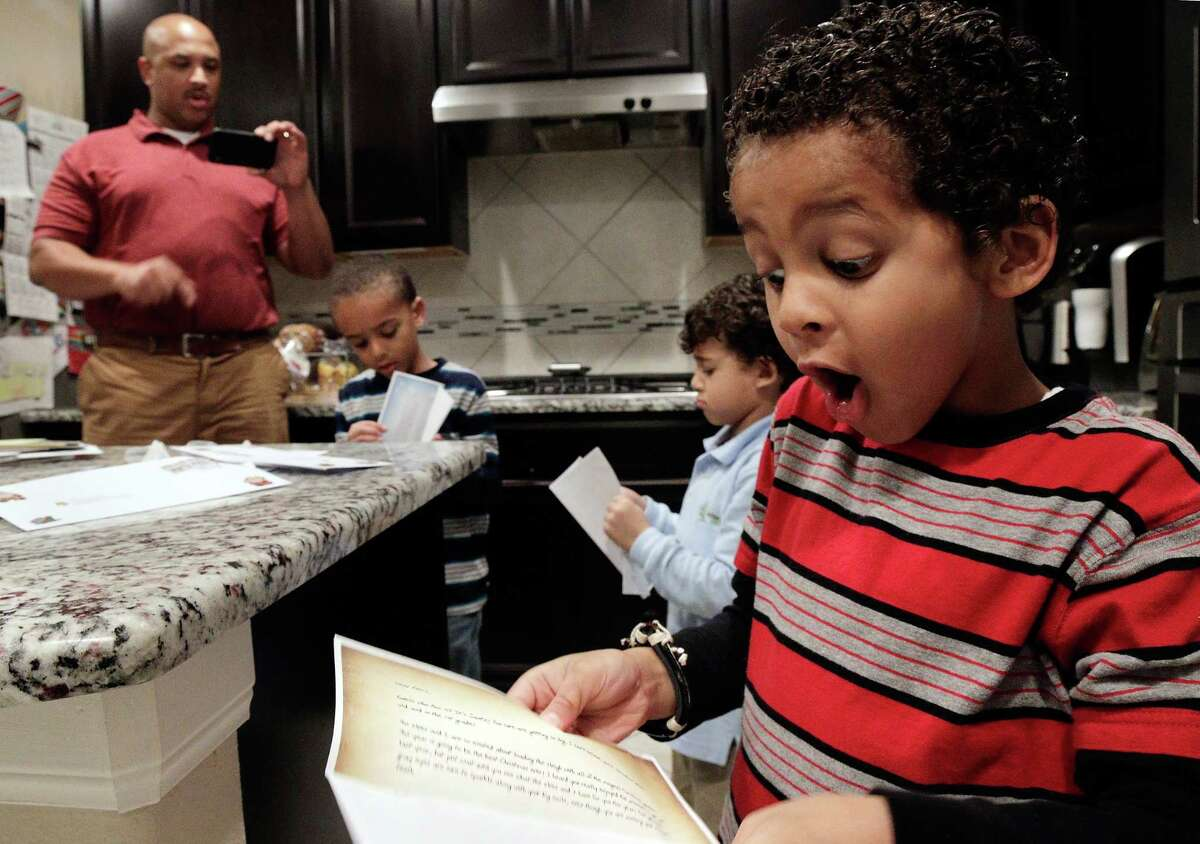 Letters from Santa are read by the Porter family in the kitchen of their home. Jason and Suzy blend their religious and cultural heritages with their three sons, Aiden, age 6 (in blue stripe shirt); Ferris, age 6 (red stripe shirt); and Zane, age 4 (light blue shirt), at their home in Richmond. Suzy, from Egypt and a Muslim, and Jason, raised Christian then converted to Muslim before marrying Suzy, mix both Muslim and Christian traditions during the holiday season. (Michael Wyke / For the Chronicle)