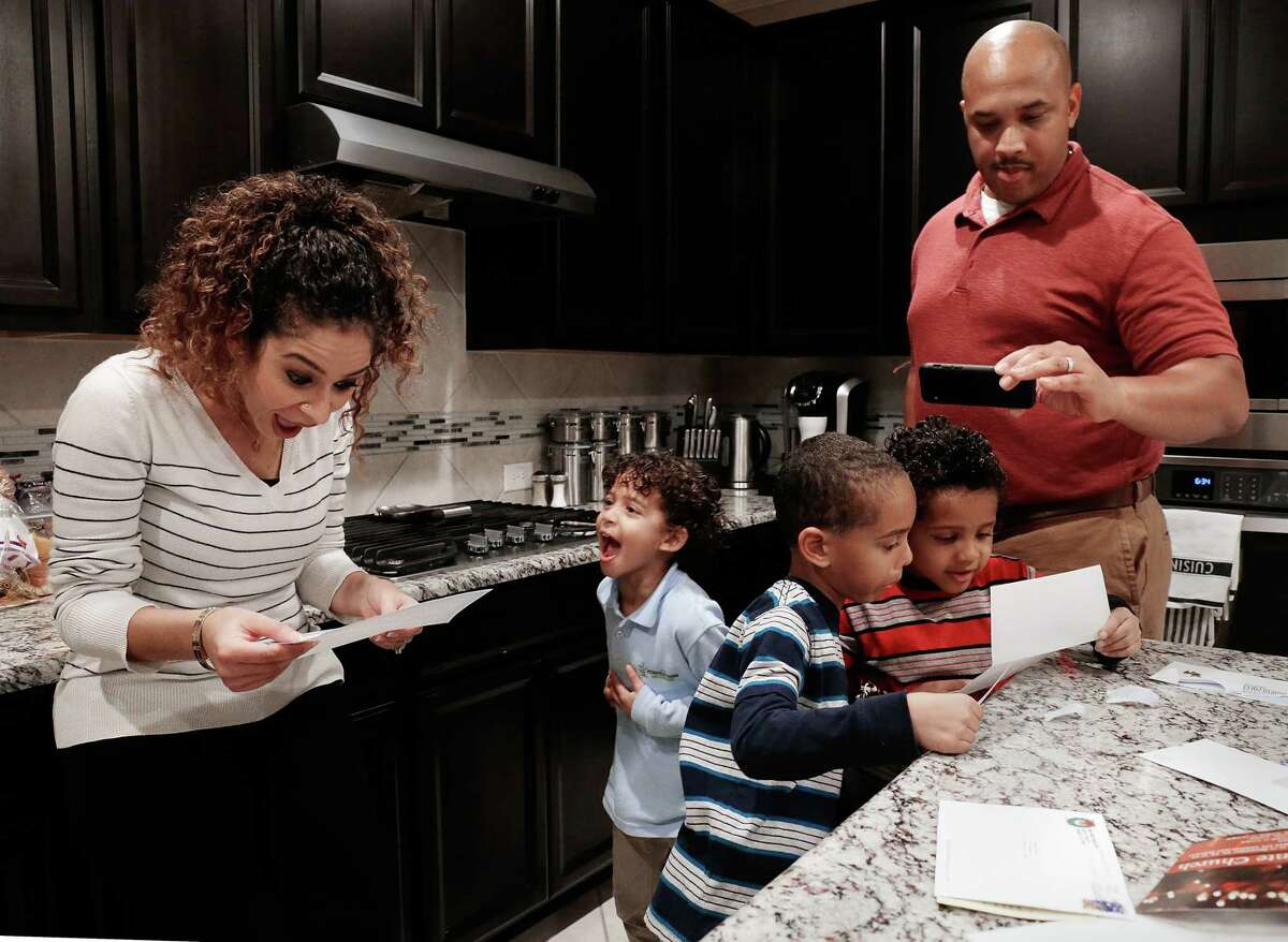 Letters from Santa are read by the Porter family in the kitchen of their home. Jason and Suzy blend their religious and cultural heritages with their three sons, Aiden, age 6 (blue stripe shirt); Ferris, age 6 (red stripe shirt); and Zane, age 4 (light blue shirt), at their home in Richmond. Suzy, from Egypt and a Muslim, and Jason, raised Christian then converted to Muslim before marrying Suzy, mix both Muslim and Christian traditions during the holiday season. (Michael Wyke / For the Chronicle)