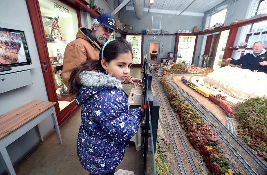 Bob Smith of West Haven and his granddaughter, Nyla Jaser, 8, of Milford activate trains at the Eli Whitney Museum's Mr. Gilbert Railroad American Flyer Trains exhibit in Hamden on December 23, 2017. Photo: Arnold Gold / Hearst Connecticut Media / New Haven Register