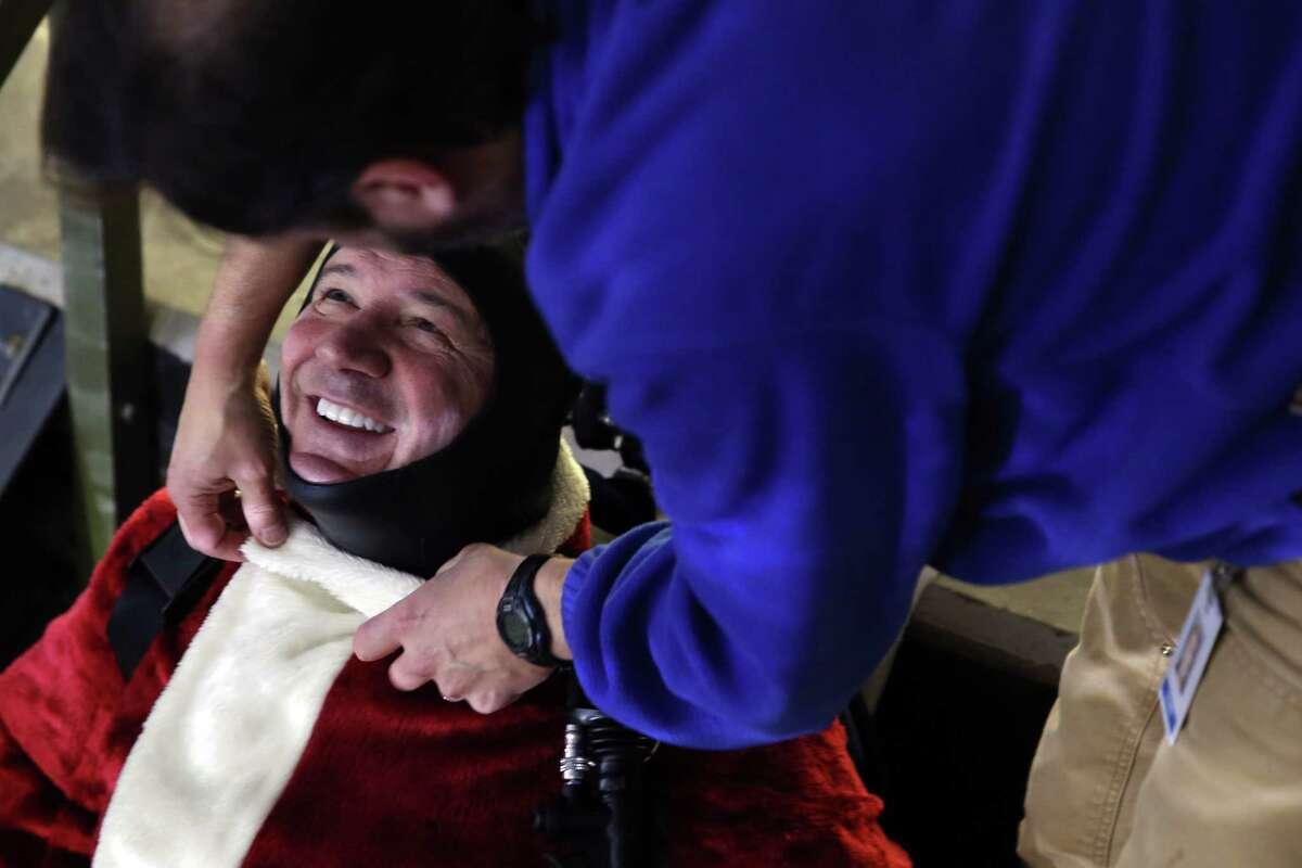 Seattle Aquarium Curator of Fish and Invertebrates Tim Carpenter helps volunteer diver Tom Griffith with his Santa Claus costume before a seasonal Christmas dive show at the Seattle Aquarium, Saturday, Dec. 23, 2017.
