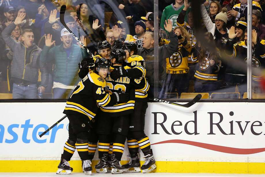 Patrice Bergeron is pinned against the glass by happy Boston teammates Torey Krug (47), Brad Marchand (63) and David Pastrnak (88) after scoring one of his two third-period goals against Detroit. Photo: Maddie Meyer, Getty Images