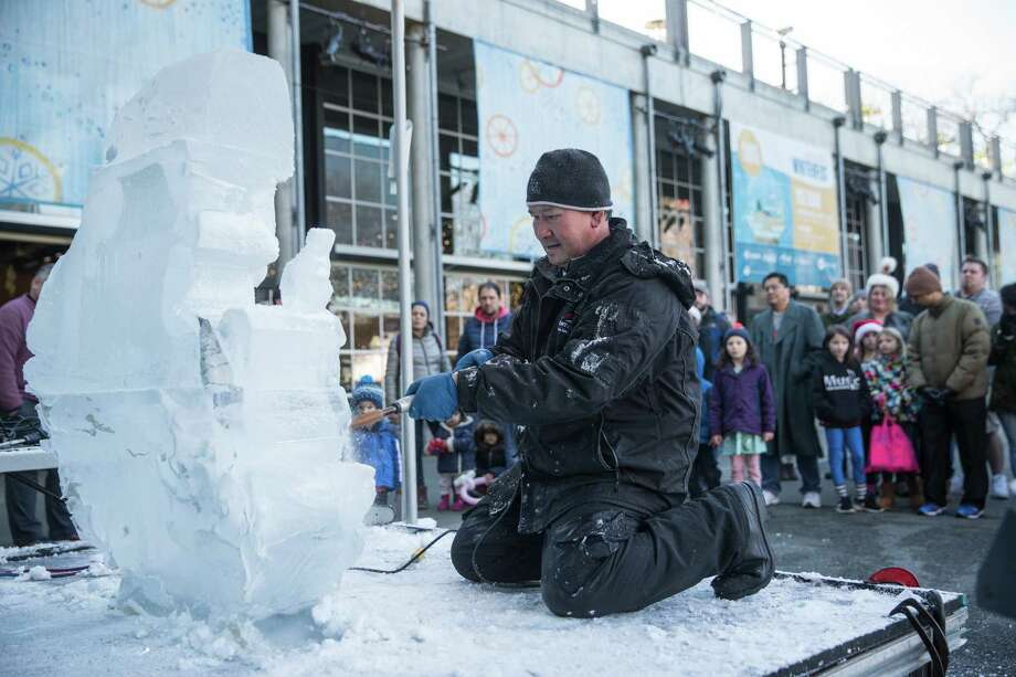 Chan Kitburi uses power tools to shape Santa Claus with an elf out of ice blocks during Winterfest at Seattle Center on Saturday, Dec. 23, 2017. Photo: GRANT HINDSLEY, SEATTLEPI.COM / SEATTLEPI.COM