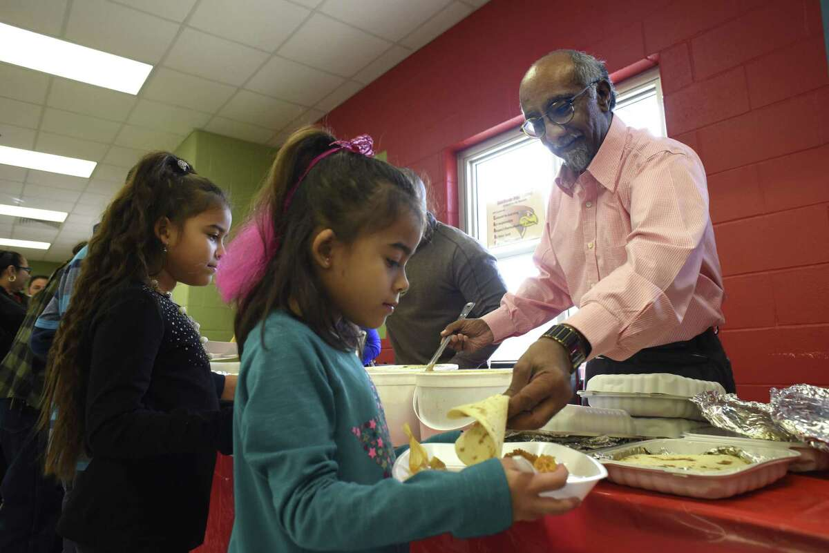 Dr. Anil T. Mangla of the University of the Incarnate Word Osteopathic Medicine program, right, serves up a tortilla to Aliah Davis, 6, during an event at the Southside Independent School District where children and their families received a tamales lunch and gifts from Santa Claus through a program put on by San Antonio philanthropist Kym Rapier.