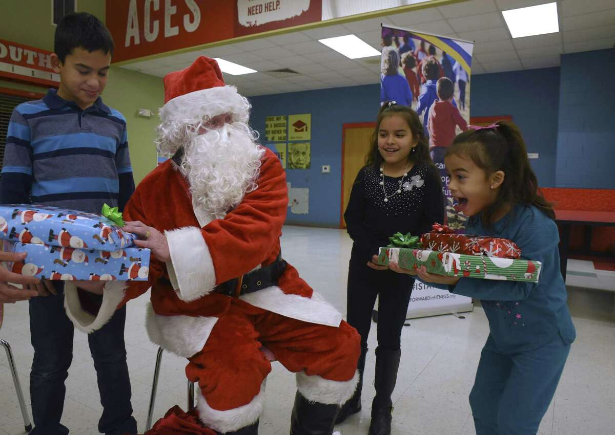 Aliah Davis, right, jumps for joy after receiving Christmas gifts from Santa Claus, who is played by Bexar County Sheriff's Office assistant chief Bobby Hogeland, during an event at the Southside Independent School District on Saturday, Dec. 23, 2017. Hogeland resigned from the sheriff's office Thursday to pursue other opportunities.
