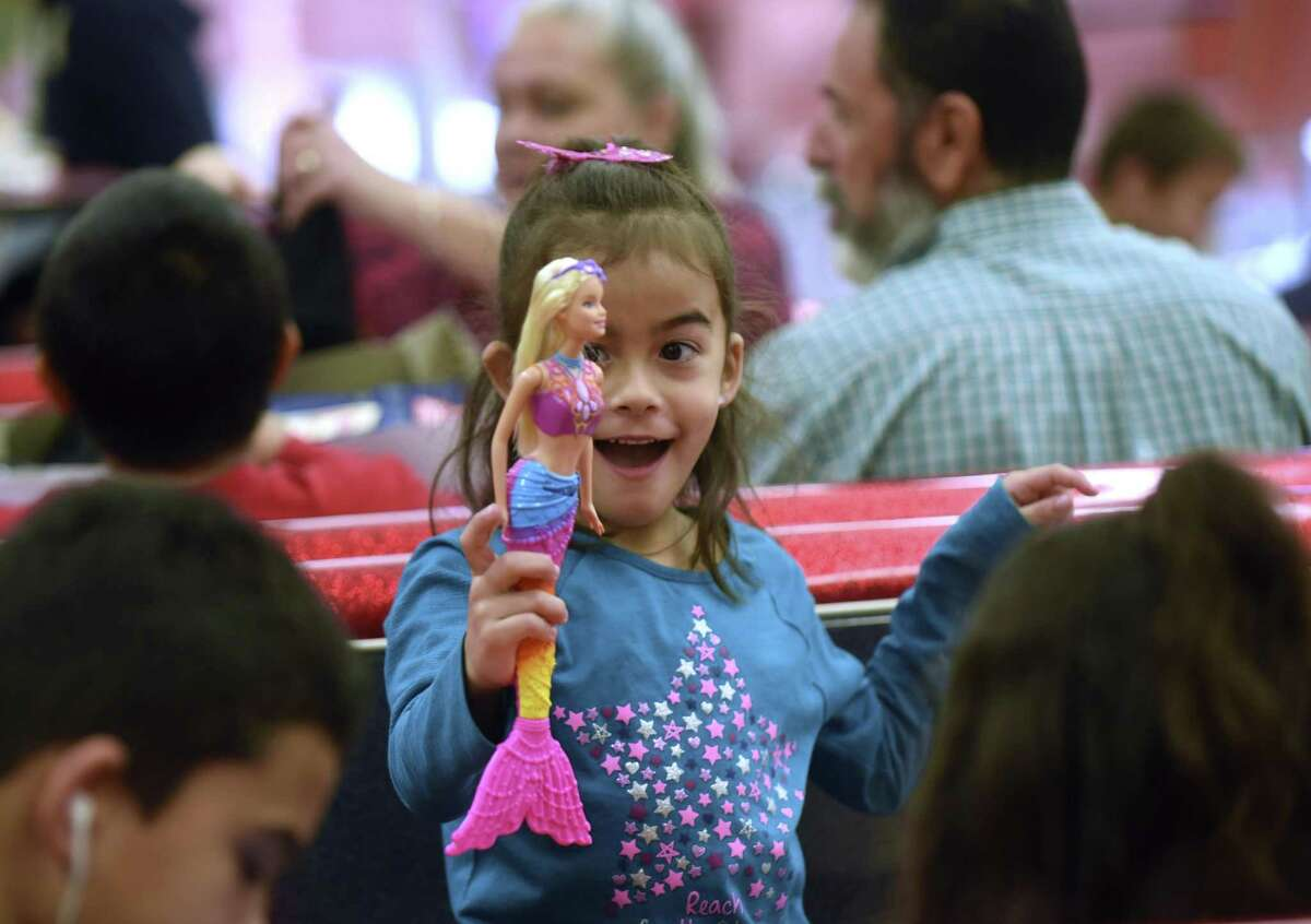Aliah Davis, 6, is thrilled after opening her Christmas gift at the Southside Independent School District on Saturday, Dec. 23, 2017. Southside children and their families received a tamales lunch and gifts from Santa Claus through a program put on by San Antonio philanthropist Kym Rapier.