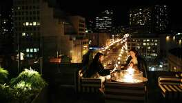 Ellie Thiele and Abby Lackner enjoy the fire on Charmaine's outdoor patio in the Proper Hotel in San Francisco on Monday, December 4, 2017.