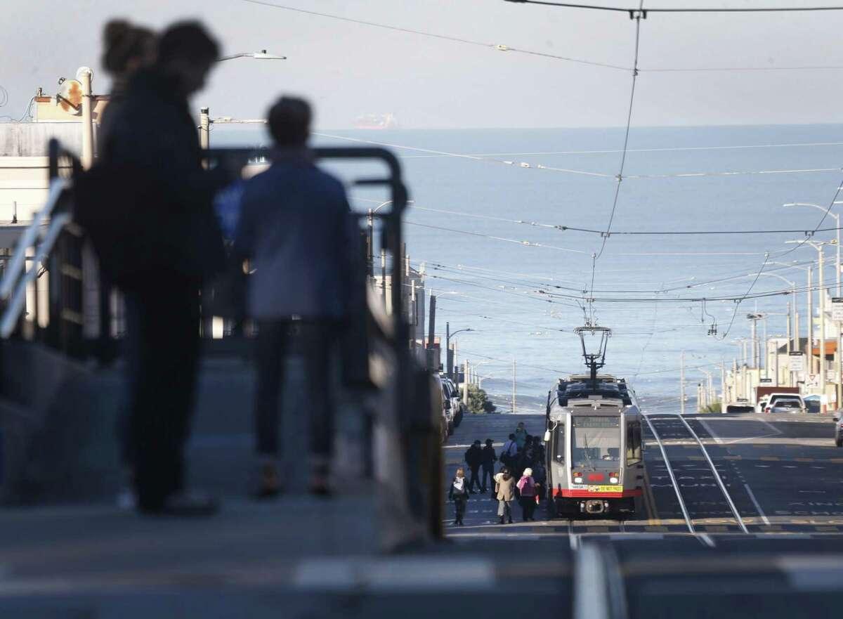 Passengers await an L-Taraval Muni Metro streetcar on Sunset Boulevard in San Francisco.