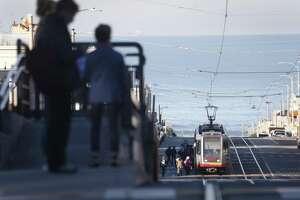 Passengers await an L-Taraval Muni Metro streetcar from a raised platform at Sunset Boulevard in San Francisco on Wednesday, December 6, 2017. The San Francisco Municipal Transportation Agency plans to install additional raised concrete boarding areas along Taraval Street.