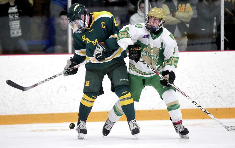 John Gethings (left) of Hamden and Clay Coassin of Notre Dame-West Haven fight for the puck in the third period at Bennett Rink in West Haven on December 23, 2017. Photo: Arnold Gold / Hearst Connecticut Media / New Haven Register